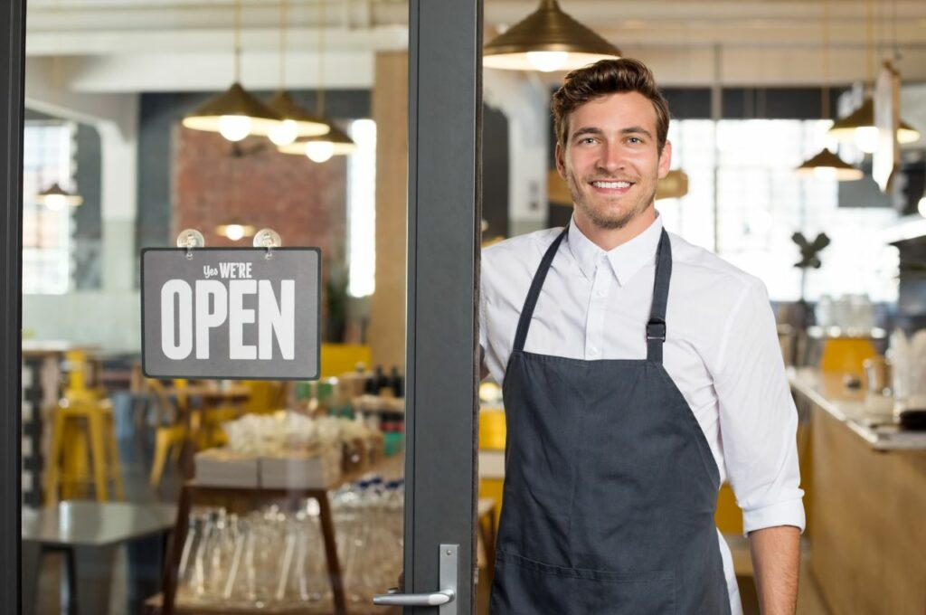 Small business owner smiling next to his store