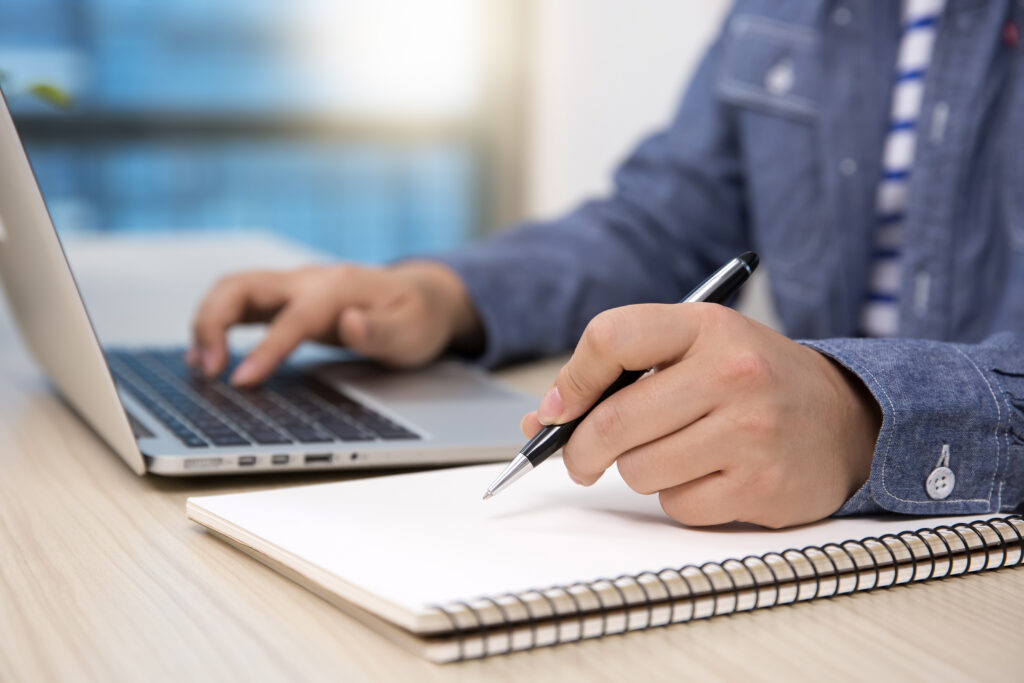 man working on computer writing notes