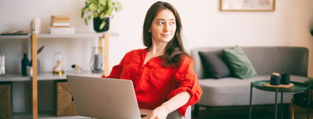 woman in a red blouse sitting with her laptop
